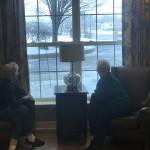 Two residents enjoy looking outside as the snow falls. They had the right idea to stay inside by the fire where it is nice and warm.