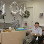 Walter is all smiles next to his 100 birthday cake and balloons!