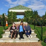 Community Life team member, Maria, poses with residents, Esther and Jean, on the atrium grounds.